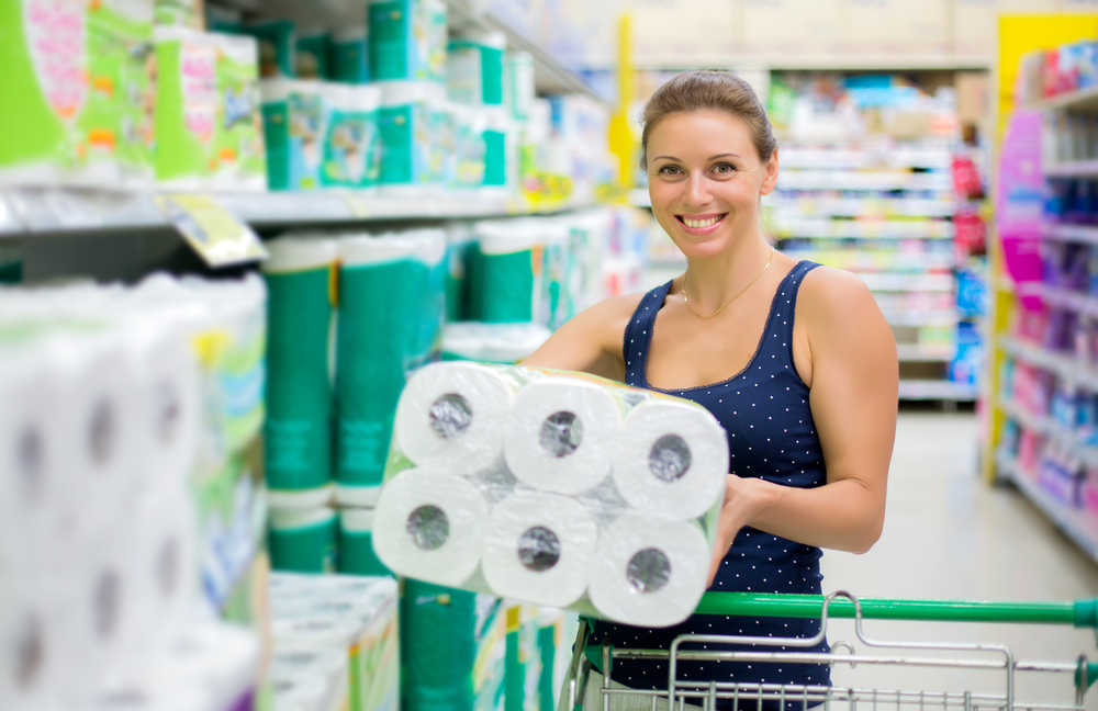 Woman chooses toilet paper in the supermarket