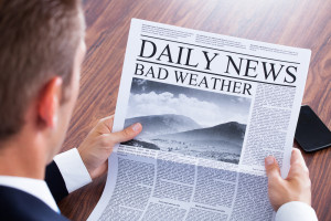 Man reads newspaper bad weather