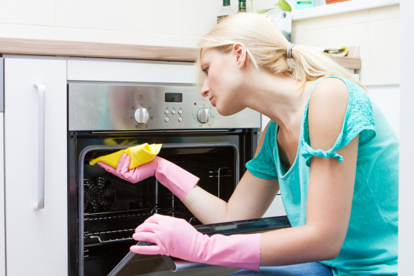 Young woman cleaning oven in the kitchen.