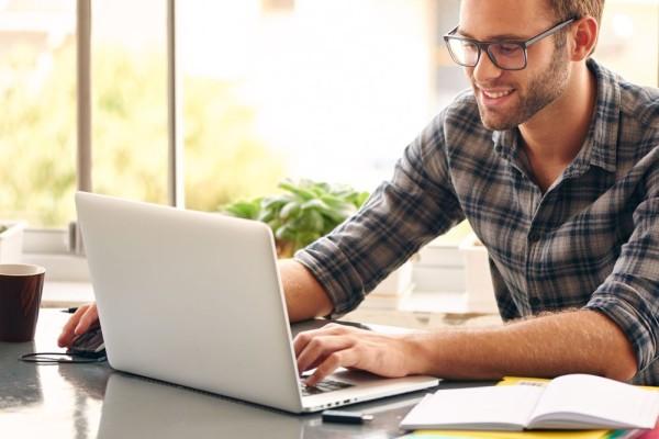 man wearing glasses works on his laptop shopping