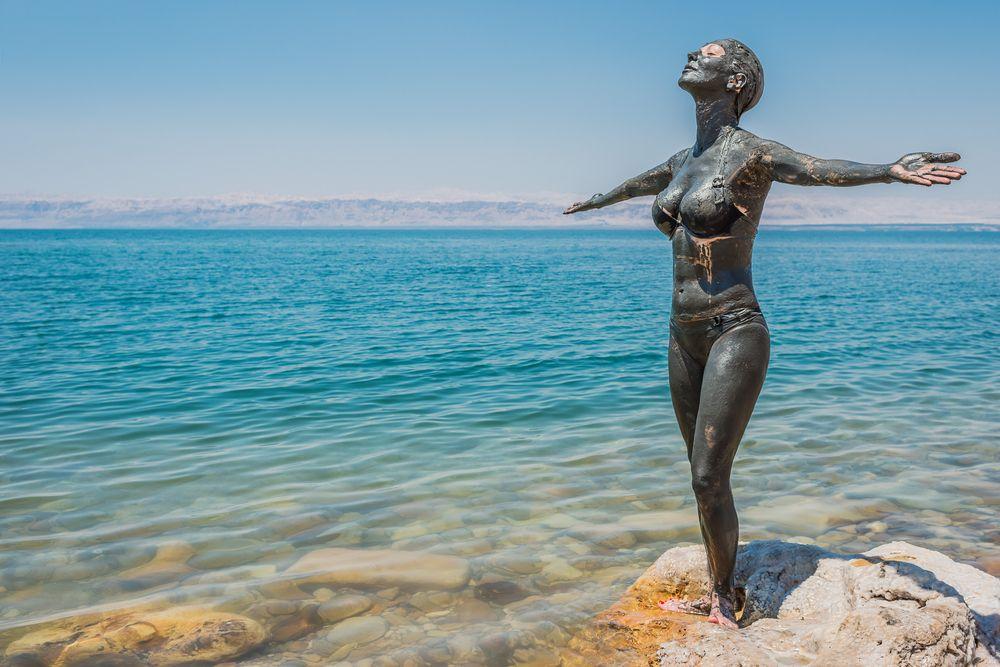 woman applying Dead Sea mud body care treatment in Jordan