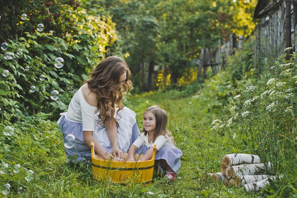 Daughter with mother washing laundry clothes in nature