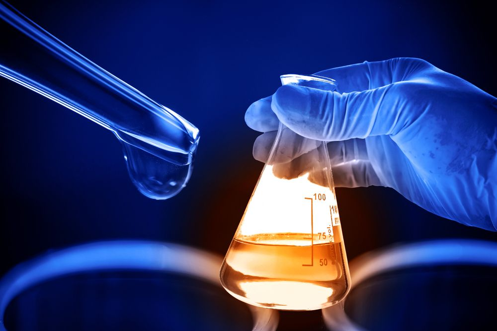 Flask in scientist hand with laboratory