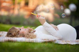 pregnant woman relaxing in park outdoors