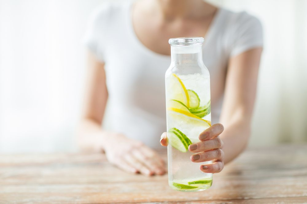 woman with fruit water in glass bottle