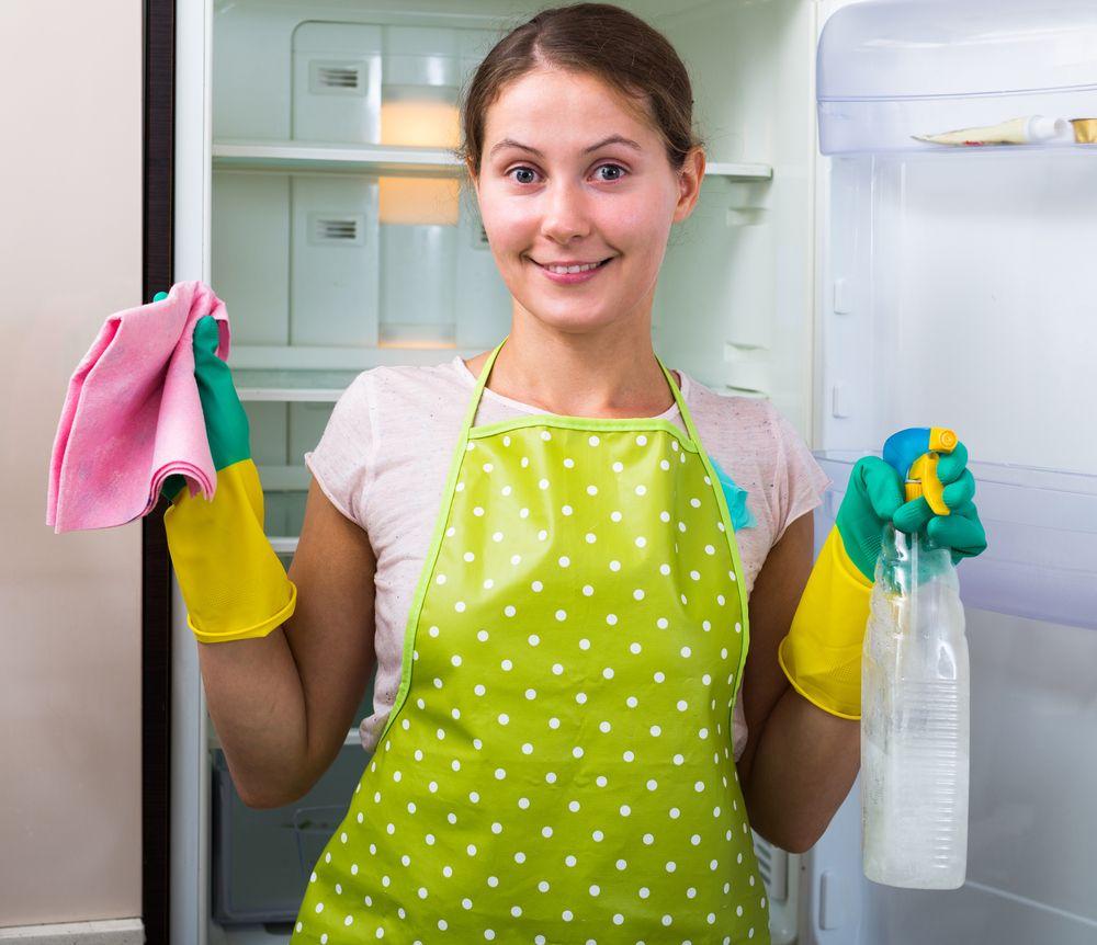 girl washing fridge shelves