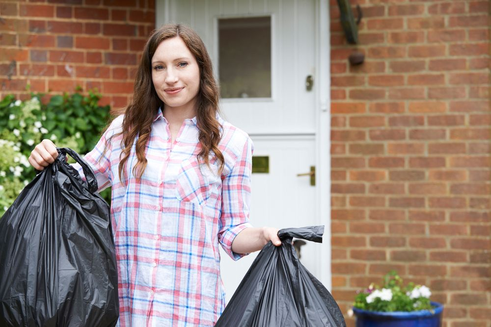 Woman Taking Out Garbage In Bags