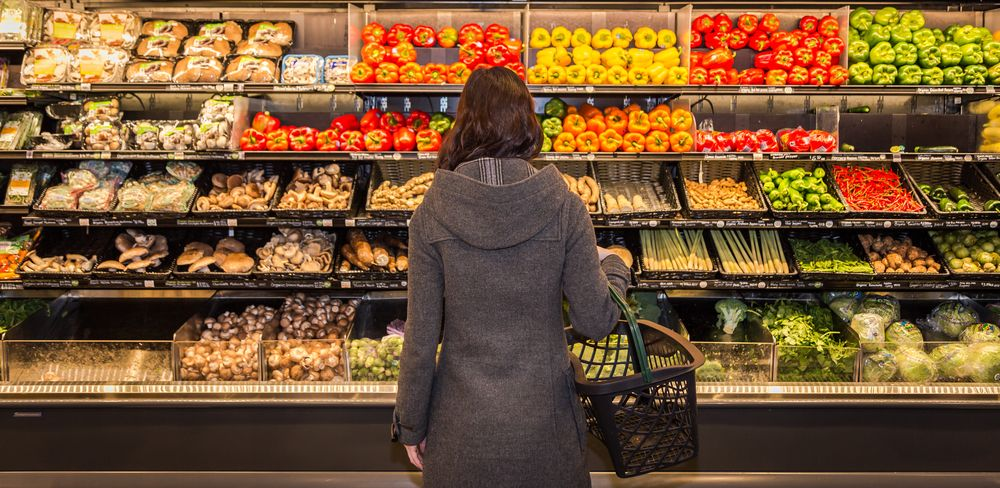 woman-standing-in-front-of-a-row-of-produce-in-a-grocery-store