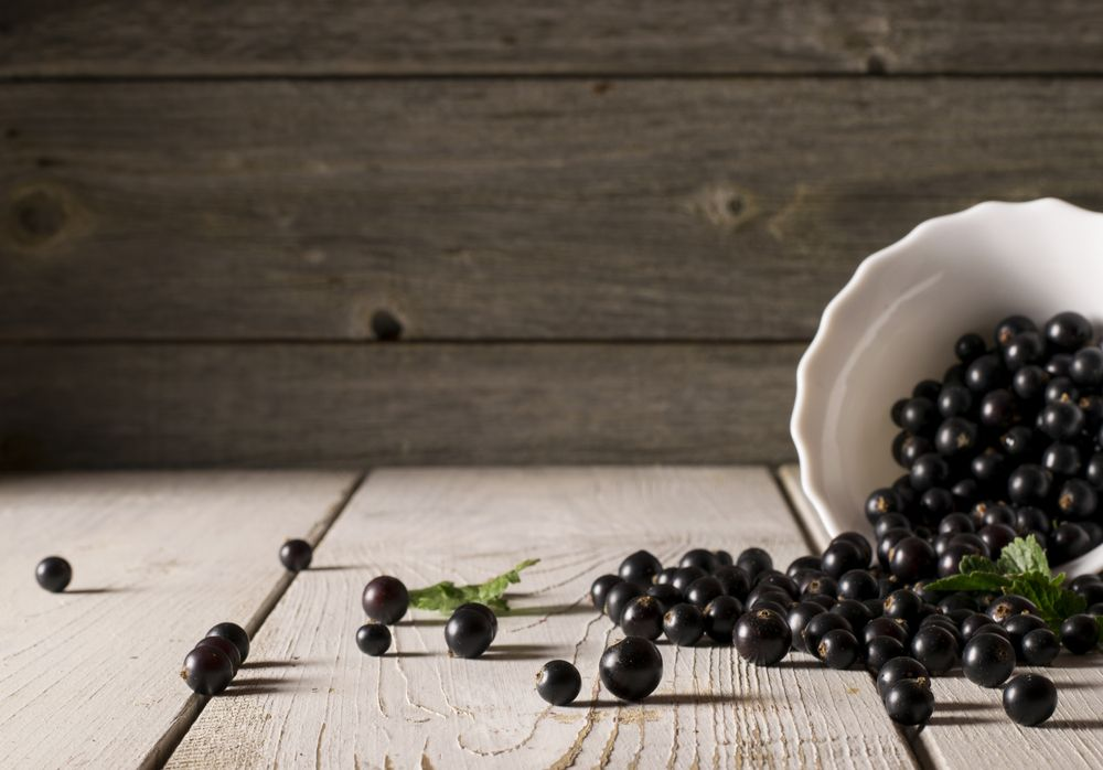 black-currant-on-wooden-table-with-leaf-sprig