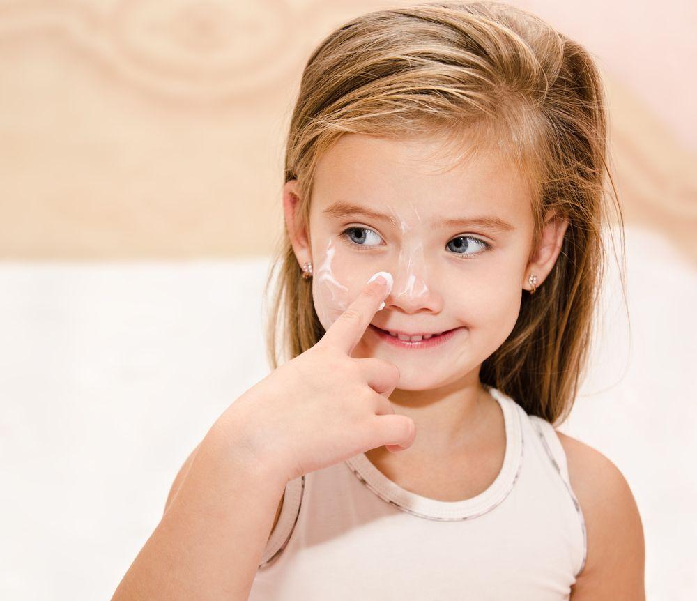 cute-smiling-little-girl-applying-cream