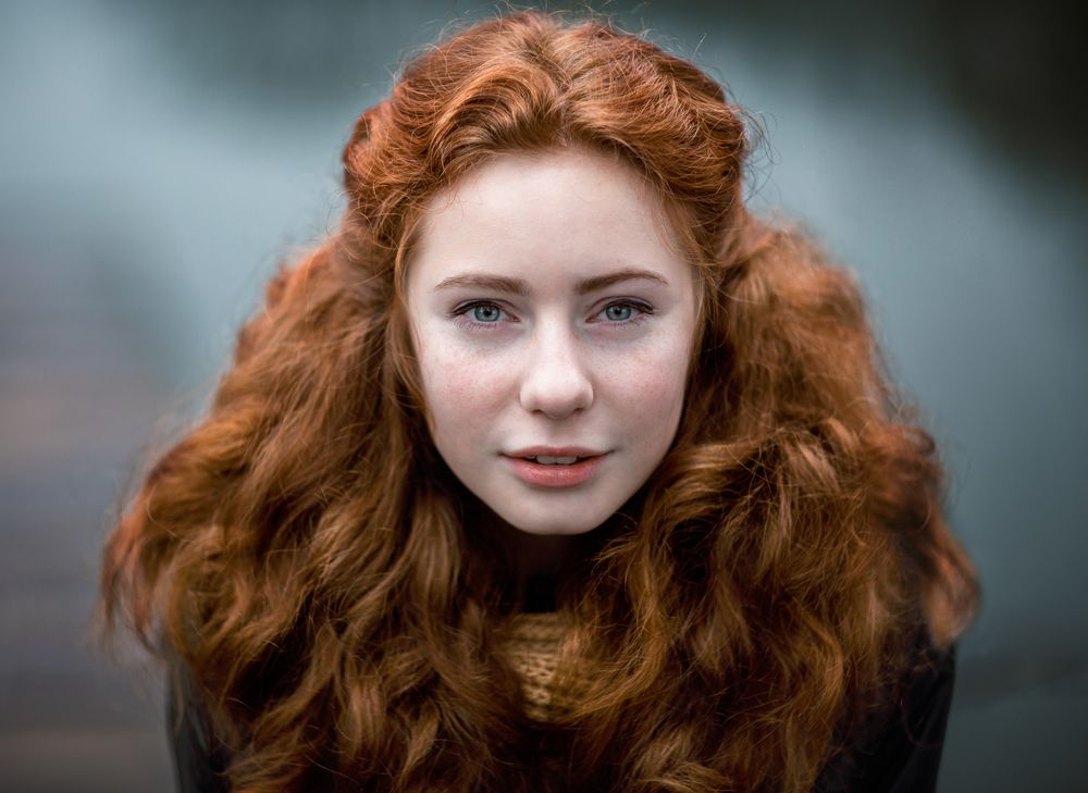 the-girl-has-red-curly-hair-voluminous-hair-the-girl-tied-a-knitted-scarf