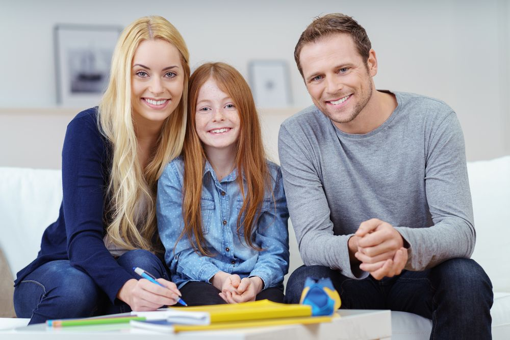 family-portrait-with-two-attractive-parents-sitting-on-either-side-of-a-pretty-vivacious-young-redhead-girl-on-the-sofa-at-home