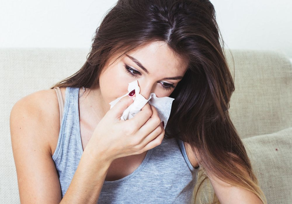 young-woman-blowing-nose-in-bed-ill-with-temperature