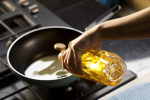 Pouring oil on frying pan maslo