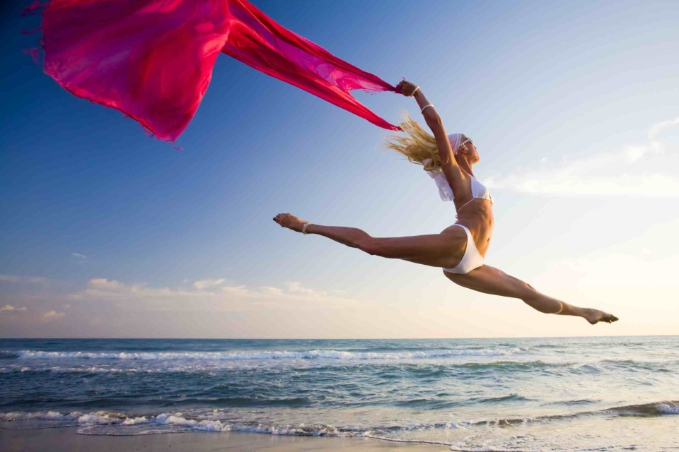Young woman with scarf jumping on beach