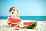 Child on the beach eating watermelon