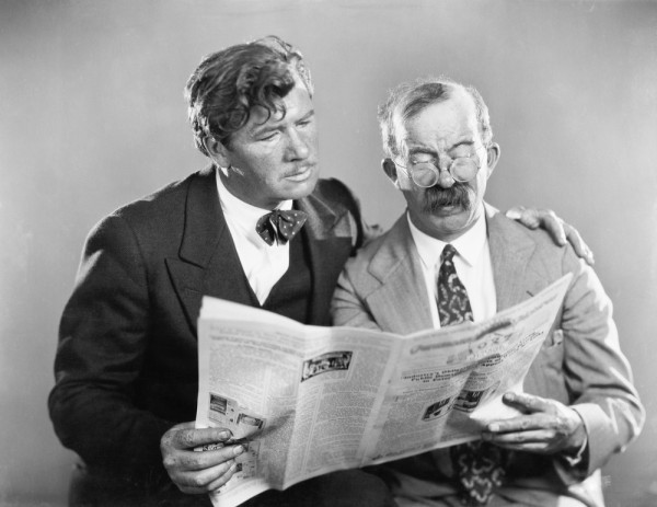 Two men read newspaper black and white