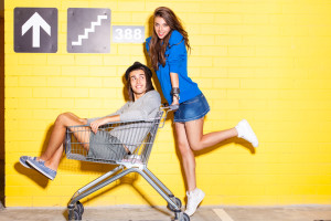 Girl boy trolley shopping yellow brick wall