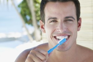 man brushes teeth toothbrush tooth paste