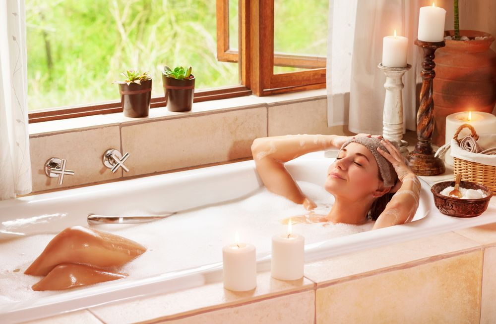 Woman relaxing at spa resort lying down in the bath