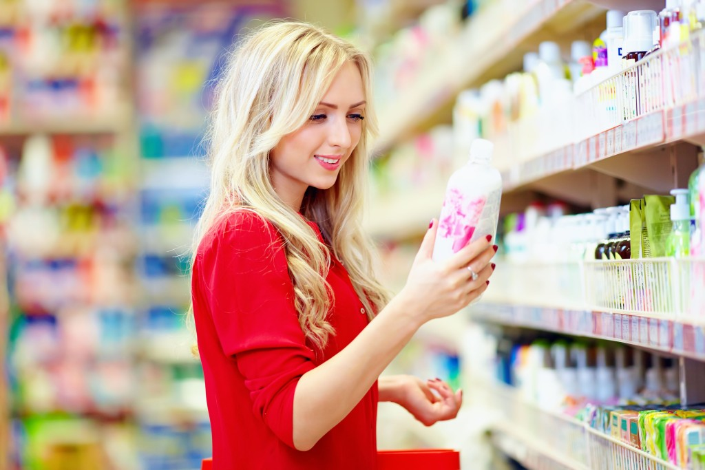 woman choosing bio eco organic personal care product in supermarket
