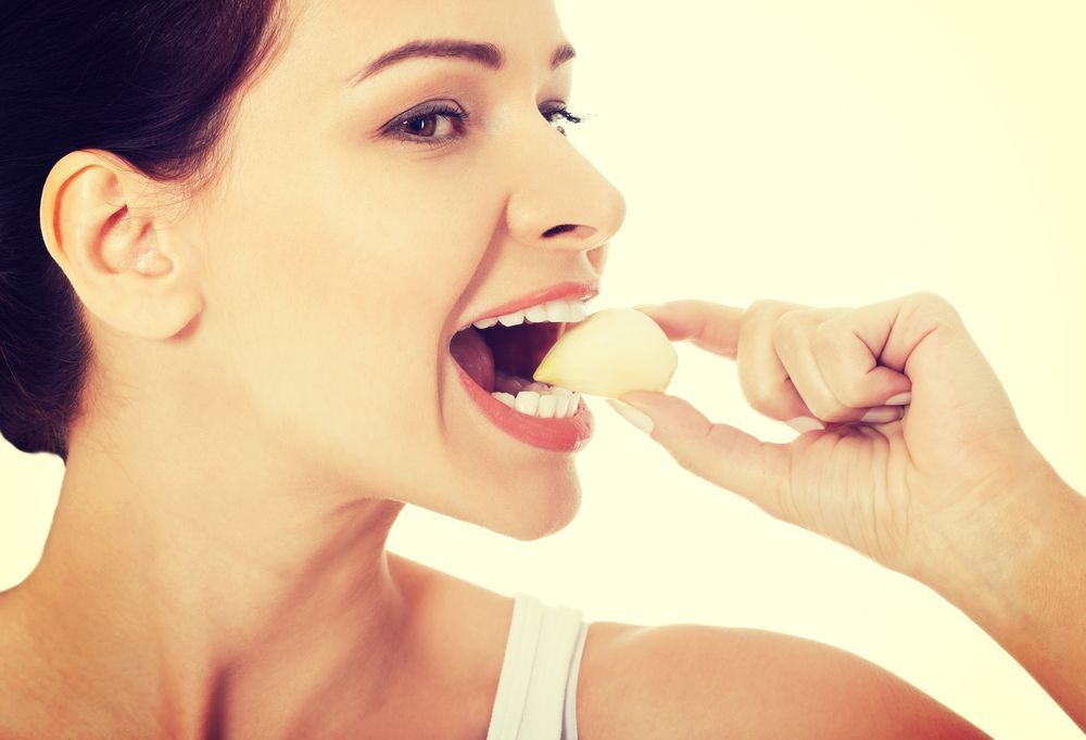 Beautiful healthy woman eating garlic