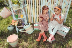 Little girls with lipstick and holding mirror in garden