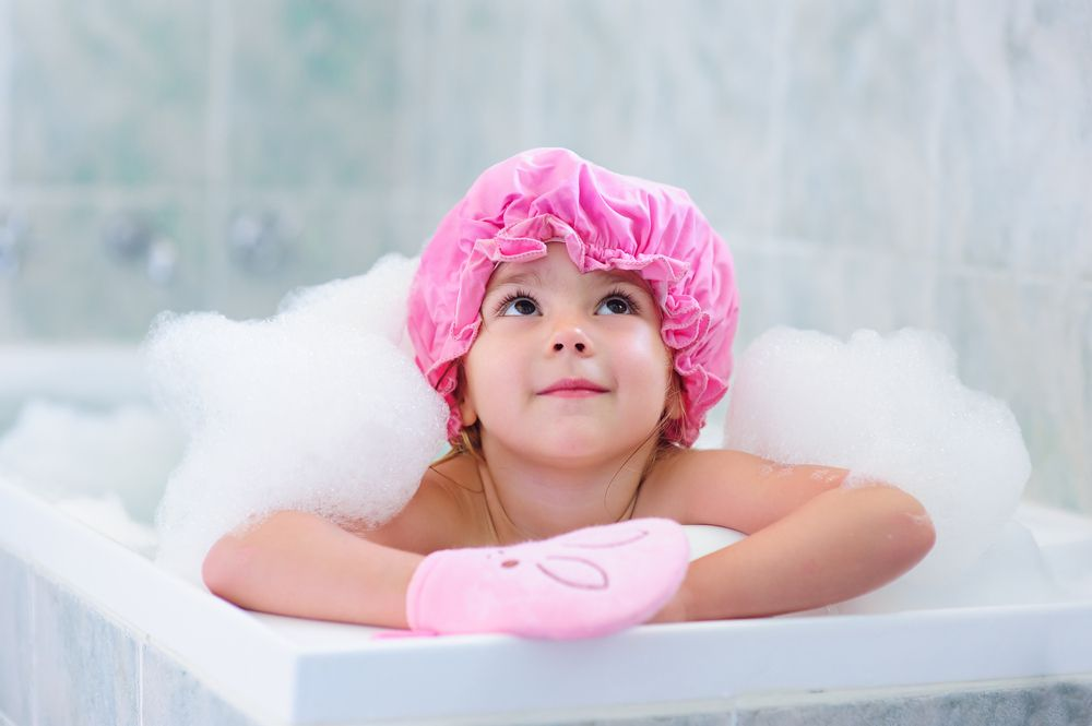 little-girl-washing-with-a-bubbles-in-bath-in-a-hat