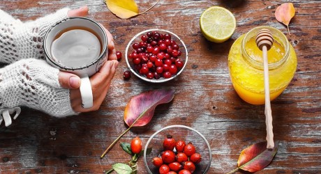 cup-in-hand-with-autumn-berry-tea-and-jar-of-honey