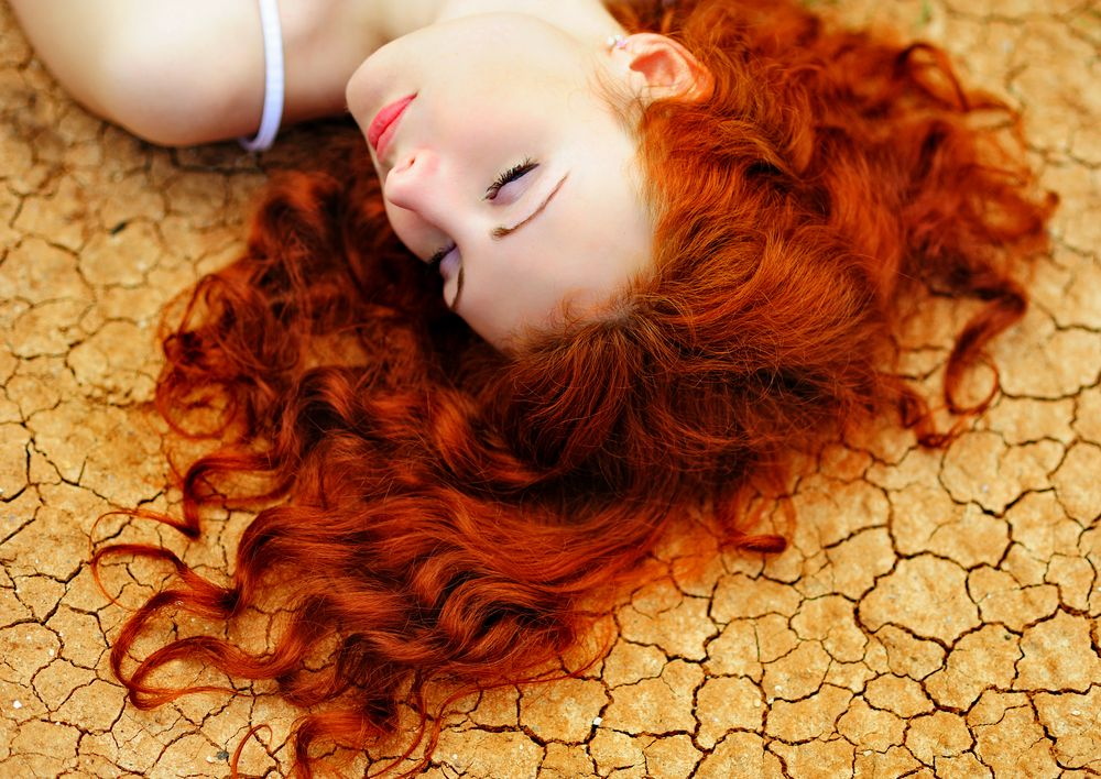 woman-with-red-hair-on-the-dried-up-ground