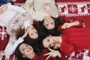 smiling-happy-girl-friends-group-in-new-years-sweater-lying-down
