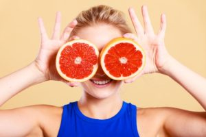 woman-girl-holding-two-halfs-of-grapefruit-citrus-fruit