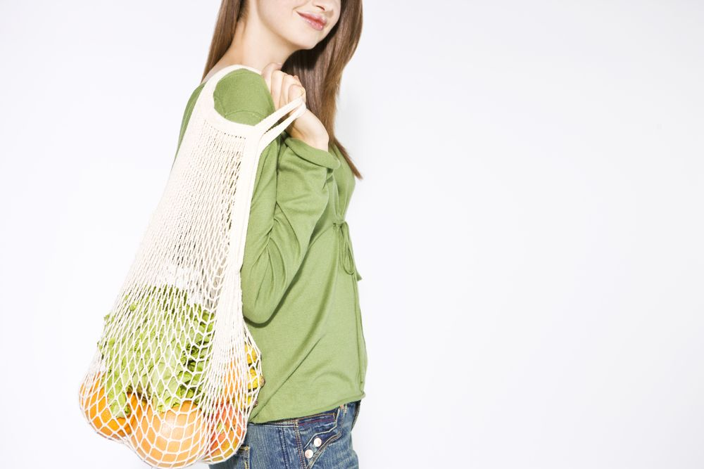 young-woman-carrying-vegetables-in-a-shopping-bag