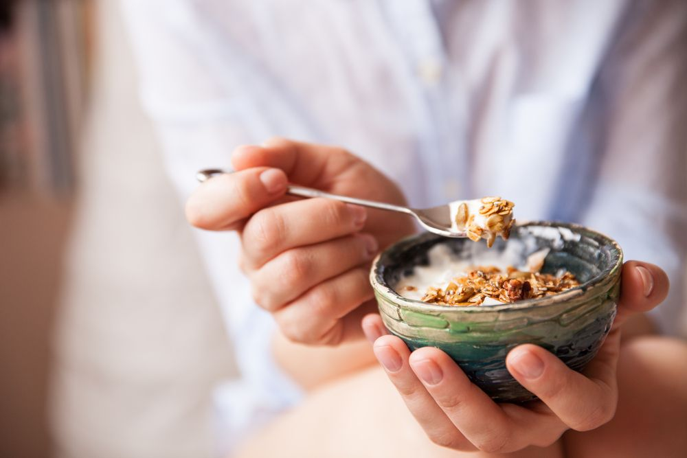 woman-with-muesli-bowl-girl-eating-breakfast