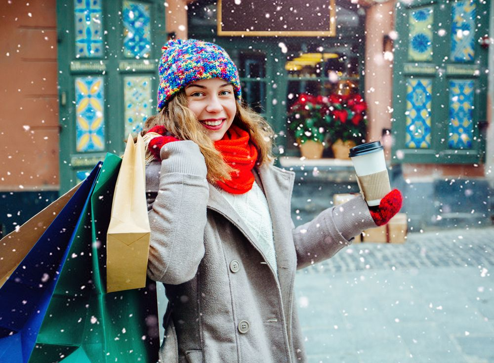 attractive-girl-with-shopping-bags-holding-disposable-cup-with-warm-drink