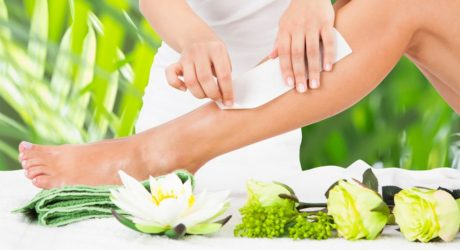 beautician-waxing-womans-leg-with-wax-strip-at-beauty-spa