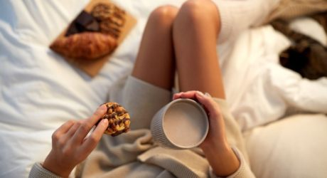 woman-with-cup-of-coffee-or-cacao-and-cookie-in-bed-at-home