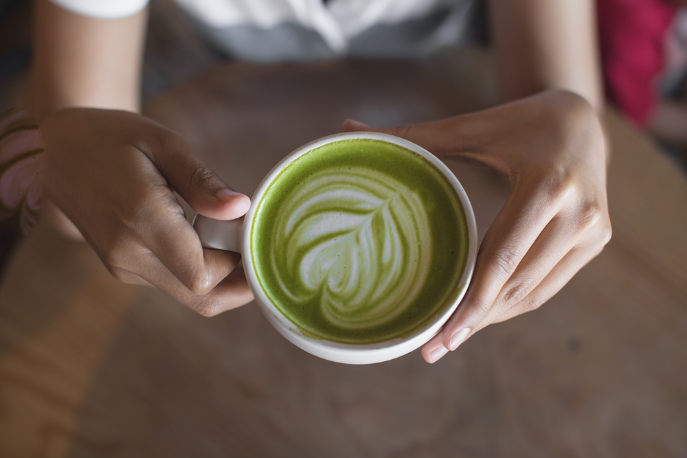 Woman holds green tea matcha latte