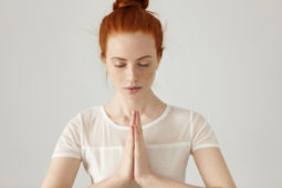 Red haired girl sitting in namaste yoga meditation