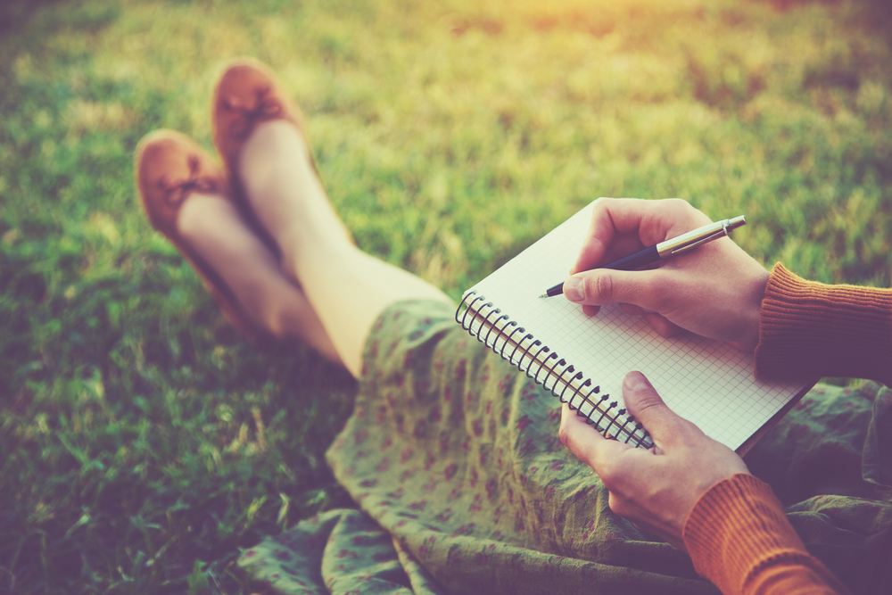 Green journalist woman with notebook and pen on grass